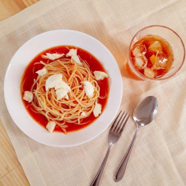 トマトを使った冷静パスタとジュースを清潔感のある白いランチョンマットの上に並べた写真